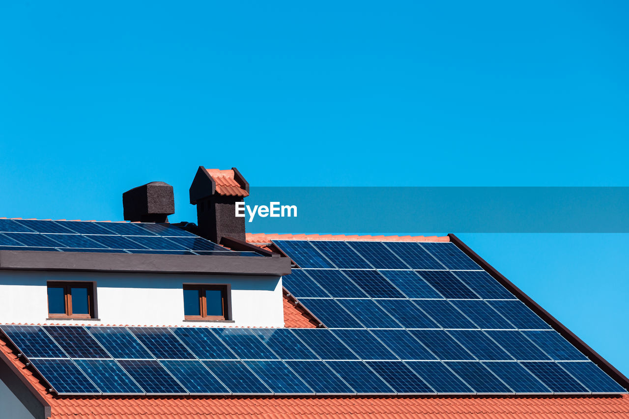 Low angle view of solar panel on house roof against blue sky