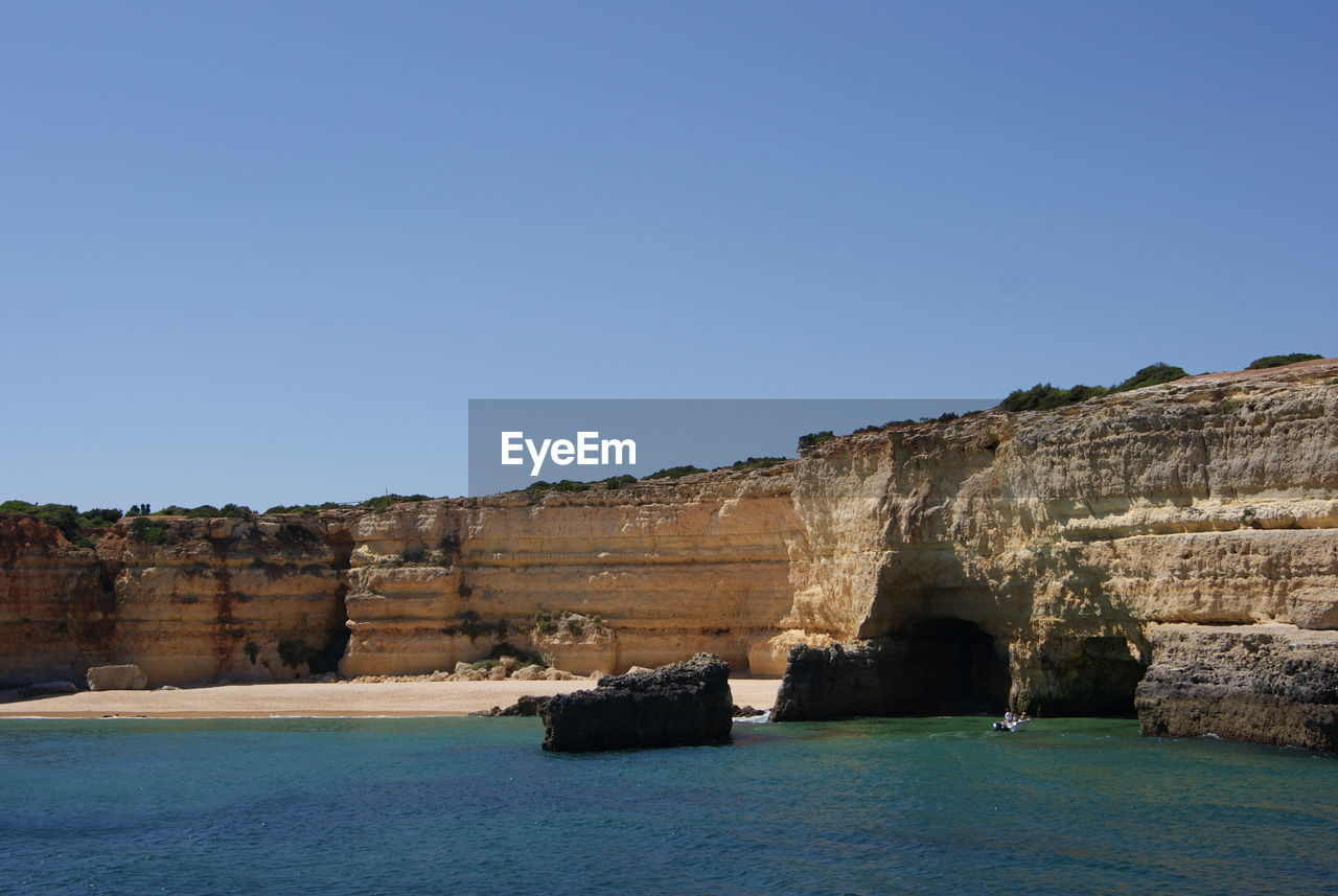 Scenic view of rock formation by sea against clear sky