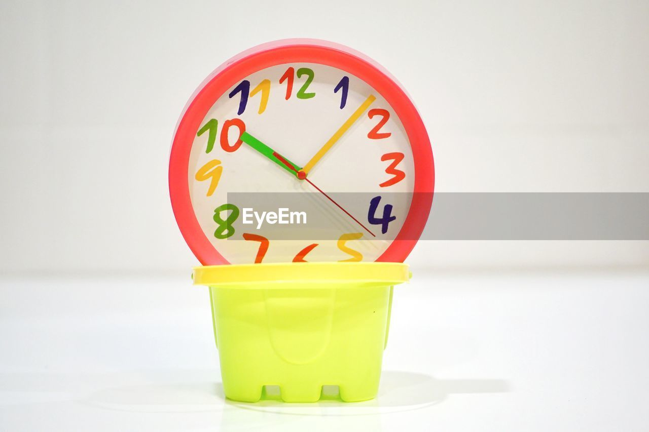clock, time, indoors, wall - building feature, no people, studio shot, green color, white background, still life, close-up, minute hand, shape, red, focus on foreground, instrument of time, number, yellow, clock face, accuracy, circle, wall clock, hour hand