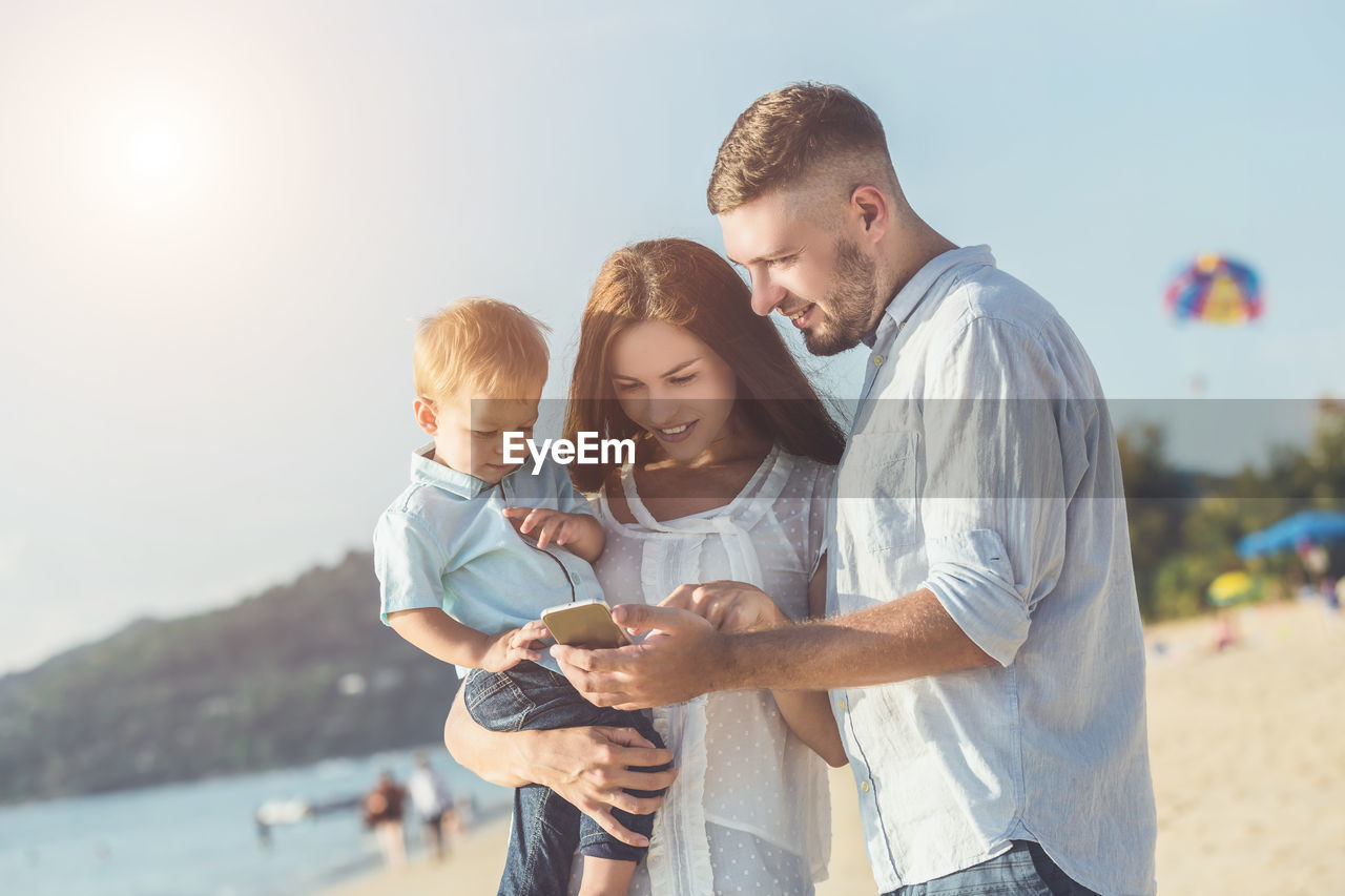 Family using mobile phone while standing at beach against sky