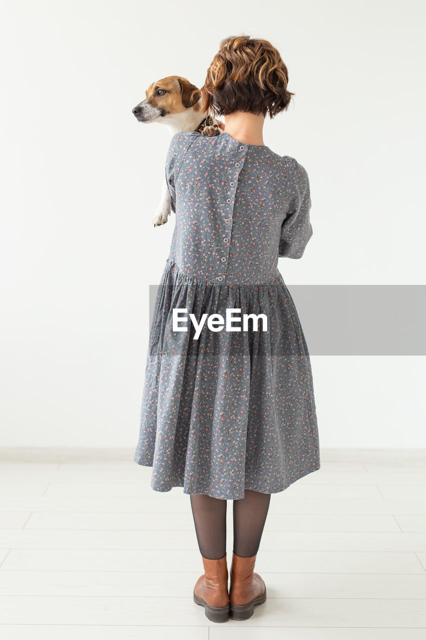 REAR VIEW OF WOMAN STANDING WITH ARMS RAISED