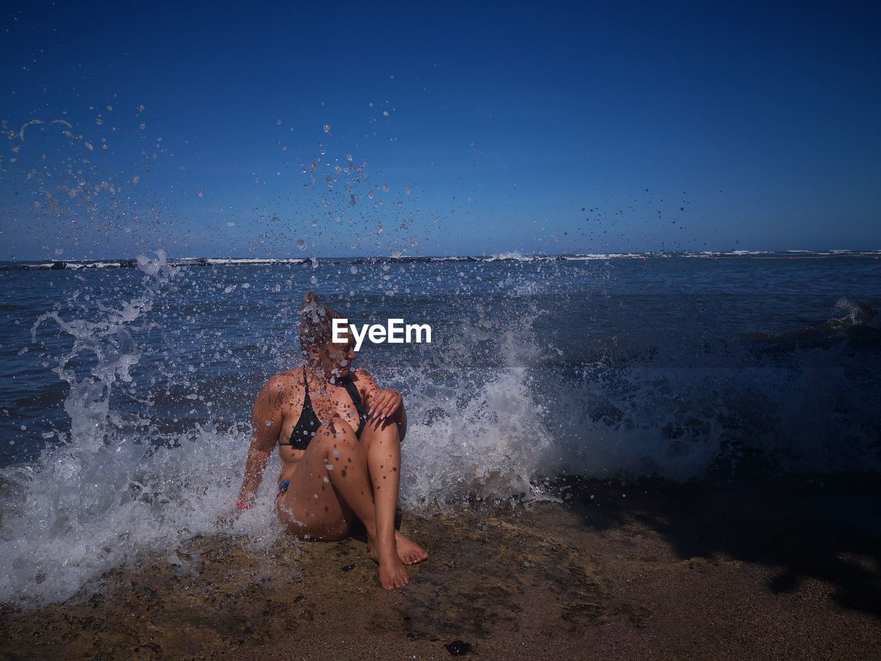 Young woman splashing water in sea against clear sky