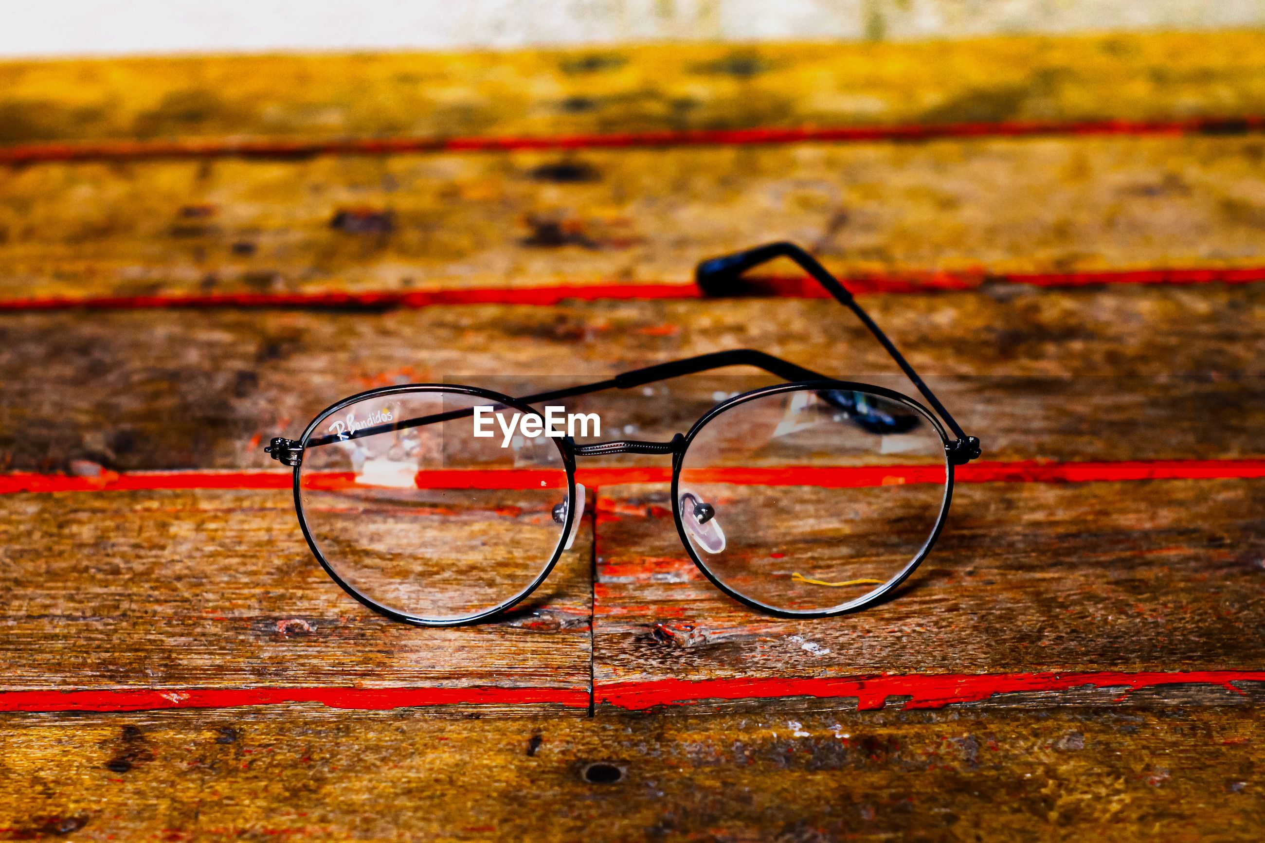 HIGH ANGLE VIEW OF EYEGLASSES ON CONCRETE WALL