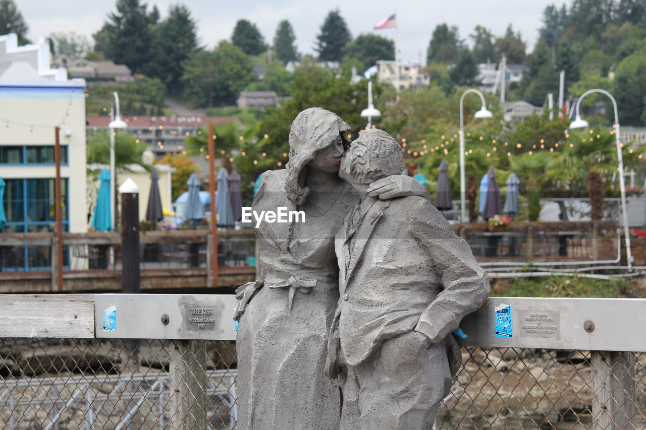 human representation, sculpture, statue, representation, focus on foreground, day, male likeness, art and craft, sadness, architecture, cemetery, nature, female likeness, grave, people, plant, creativity, tree, emotion, outdoors