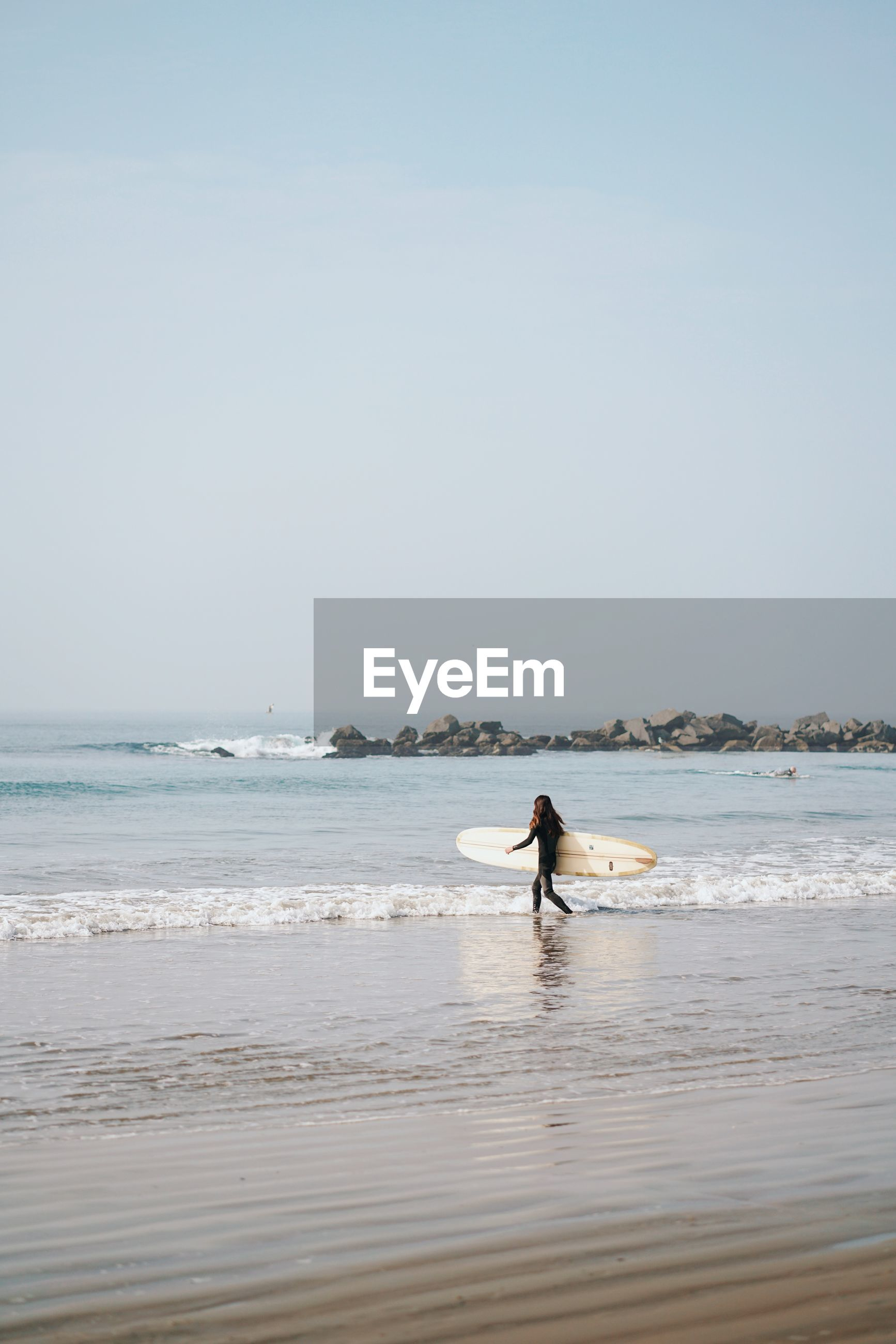 Woman with surfboard walking towards sea against clear sky