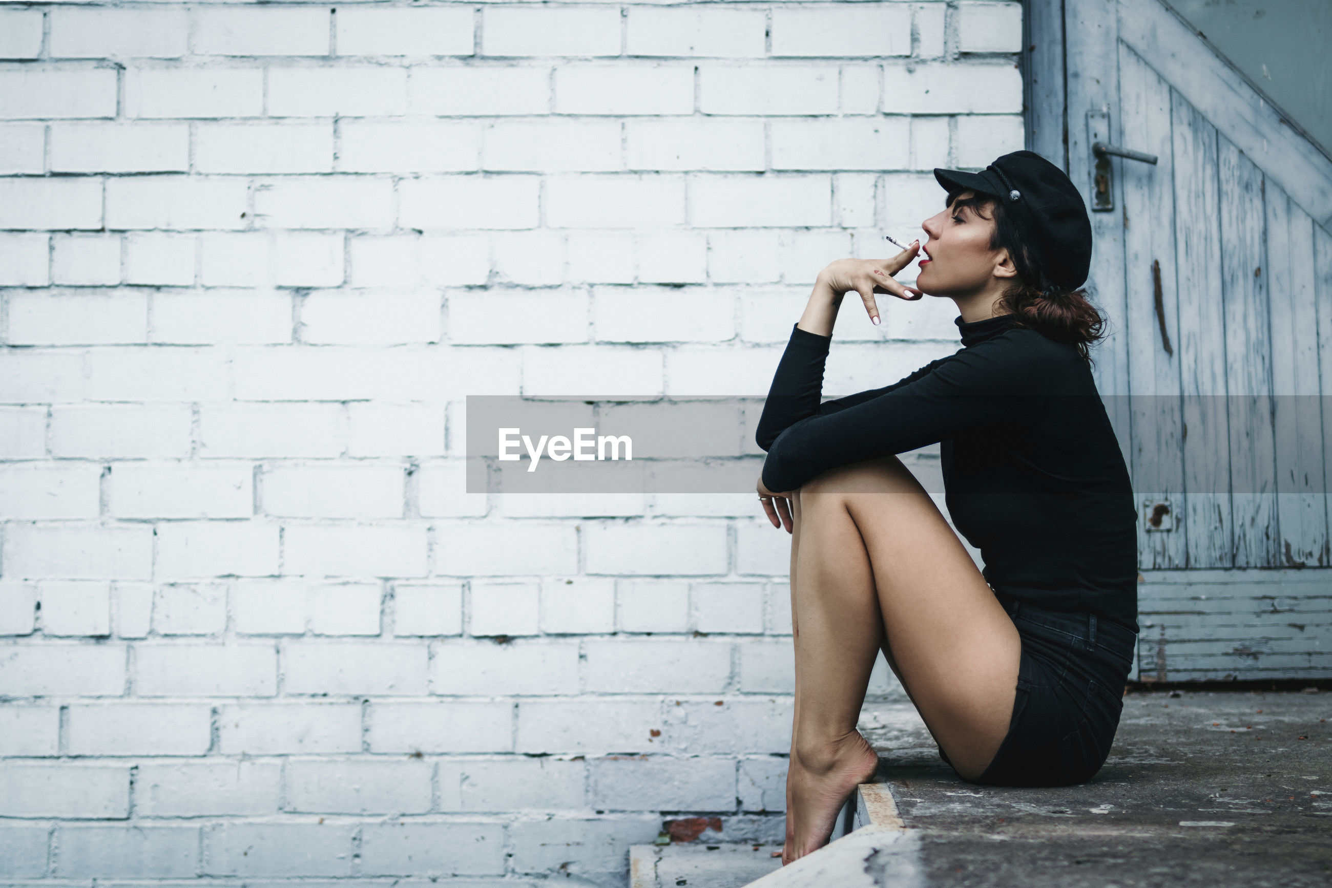 Side view of mid adult woman smoking while sitting against brick wall