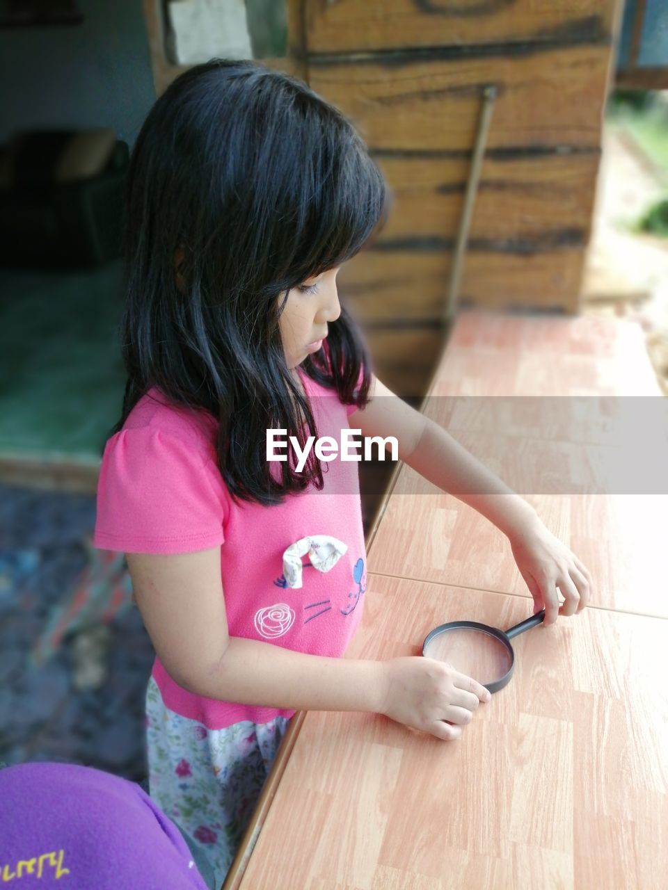 Cute girl standing holding magnifying glass on table