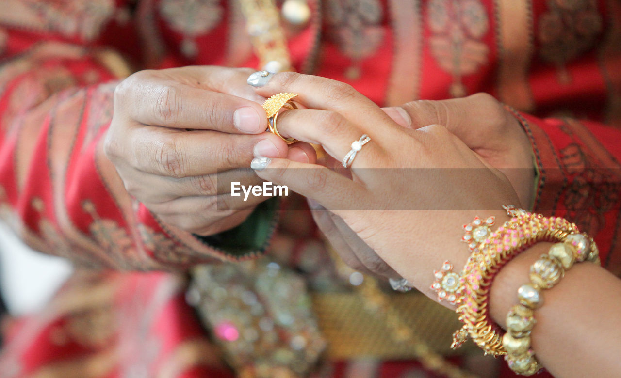 Midsection Of Wedding Couple Exchanging Finger Rings During Ceremony