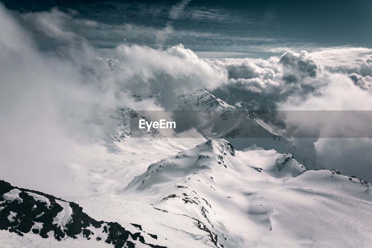 cloud - sky, beauty in nature, scenics - nature, sky, cold temperature, tranquil scene, snow, winter, tranquility, mountain, non-urban scene, environment, nature, snowcapped mountain, white color, landscape, no people, day, mountain range, outdoors, mountain peak