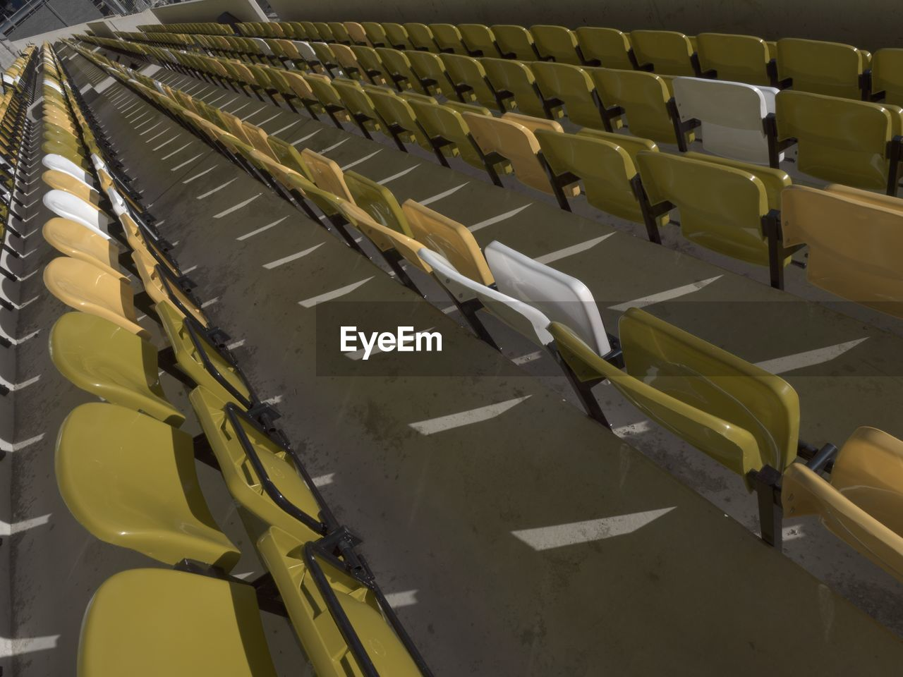 seat, chair, in a row, empty, absence, repetition, no people, stadium, side by side, high angle view, large group of objects, auditorium, arrangement, sport, order, indoors, bleachers, theater, yellow, day, foldable