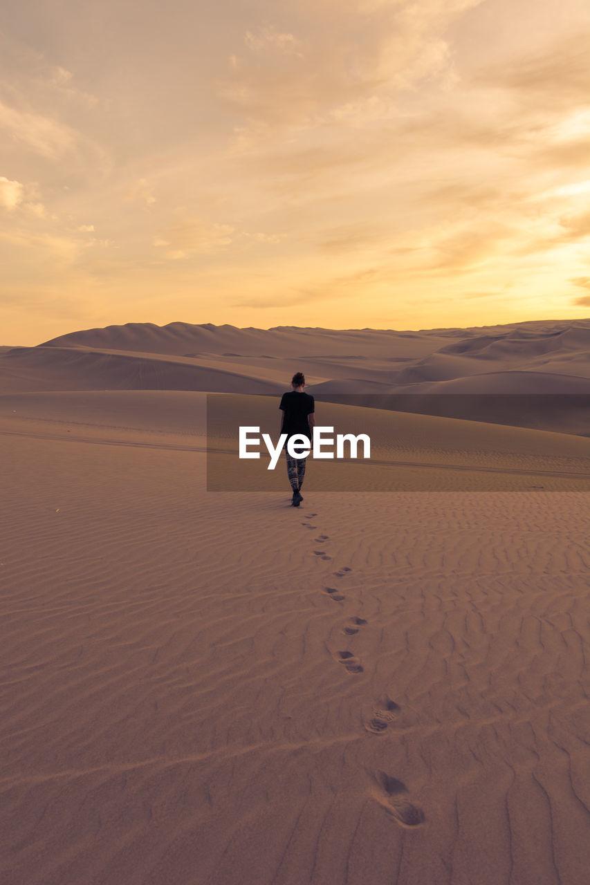 Rear View Of Woman Walking In Desert