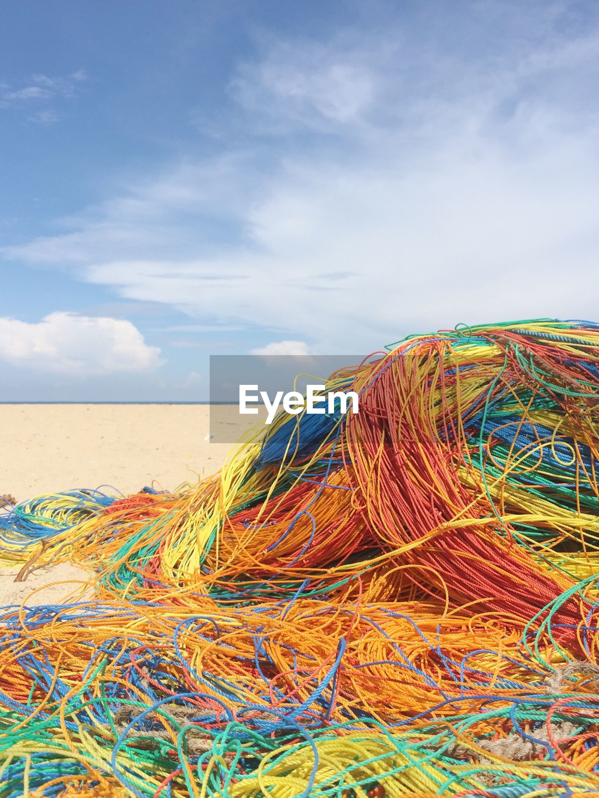 Stack of colorful ropes at beach against sky