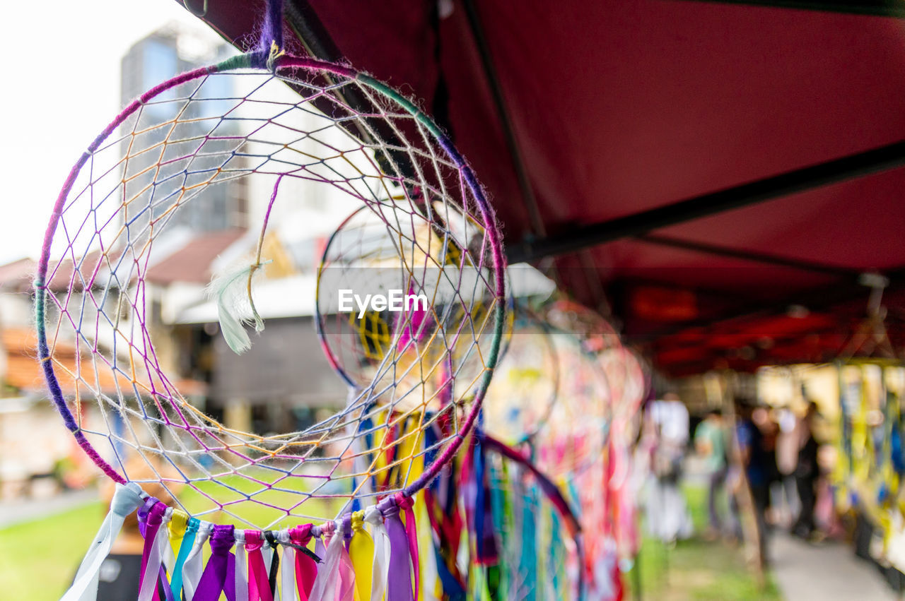 multi colored, focus on foreground, close-up, day, incidental people, hanging, outdoors, dreamcatcher, art and craft, lifestyles, selective focus, decoration, people, women, shape, arts culture and entertainment, craft, group, ceiling