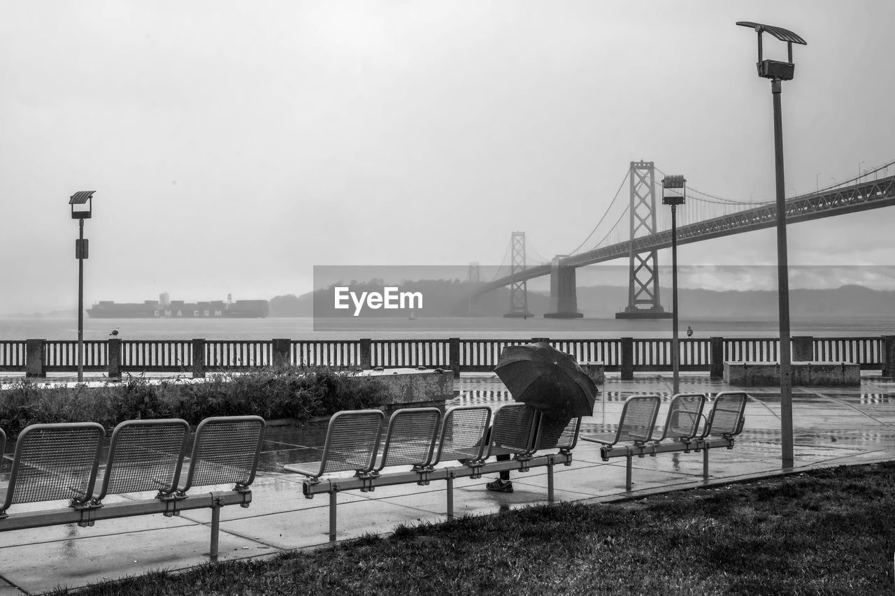 Person With Umbrella By Bay Bridge Against Sky During Rainy Season