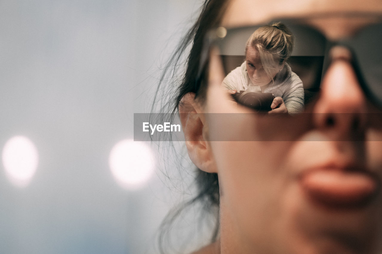 Close-Up Of Woman Wearing Sunglasses With Female Friend Photographing At Home