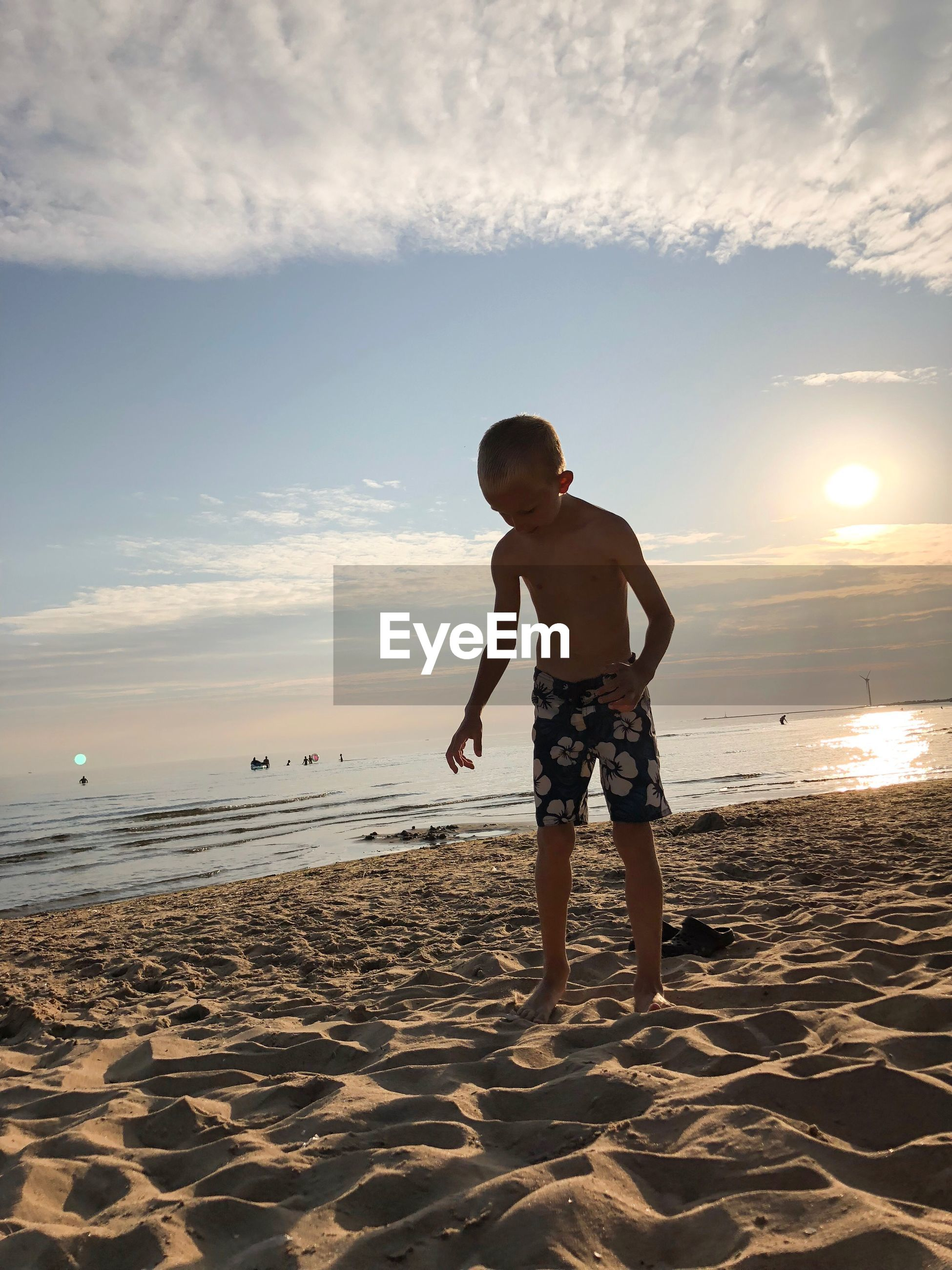 Shirtless boy standing at beach against sky during sunset