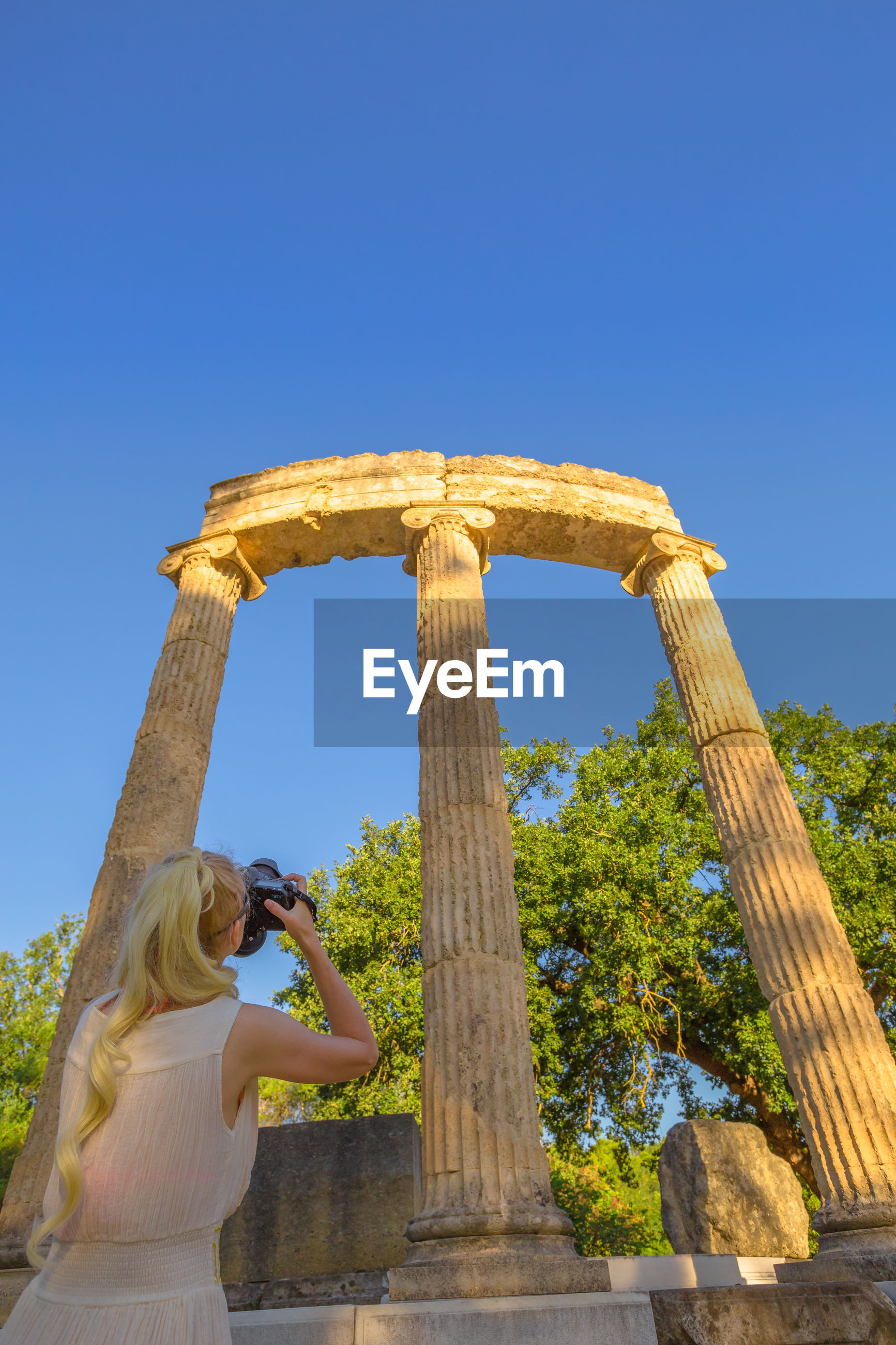 Rear view of woman photographing columns against clear blue sky