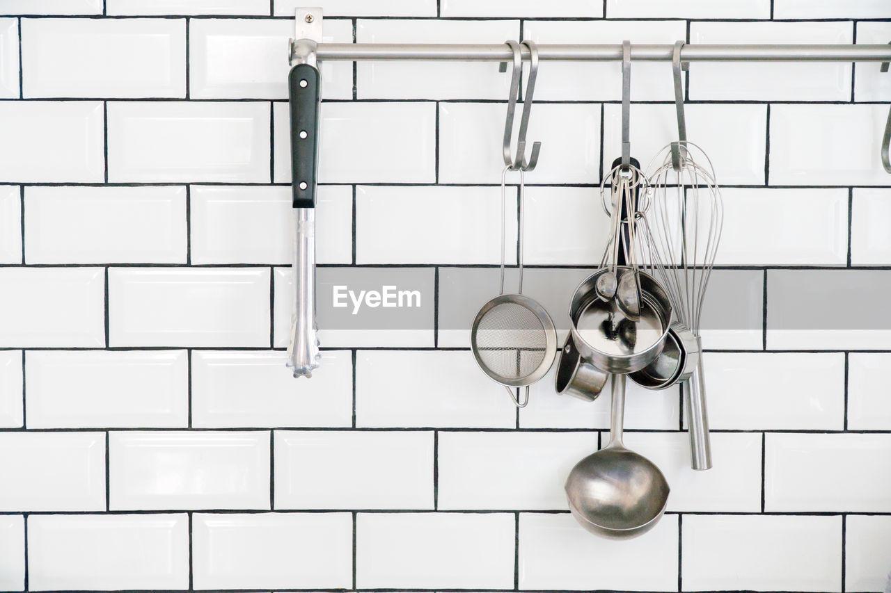 Kitchen utensils hanging against white wall