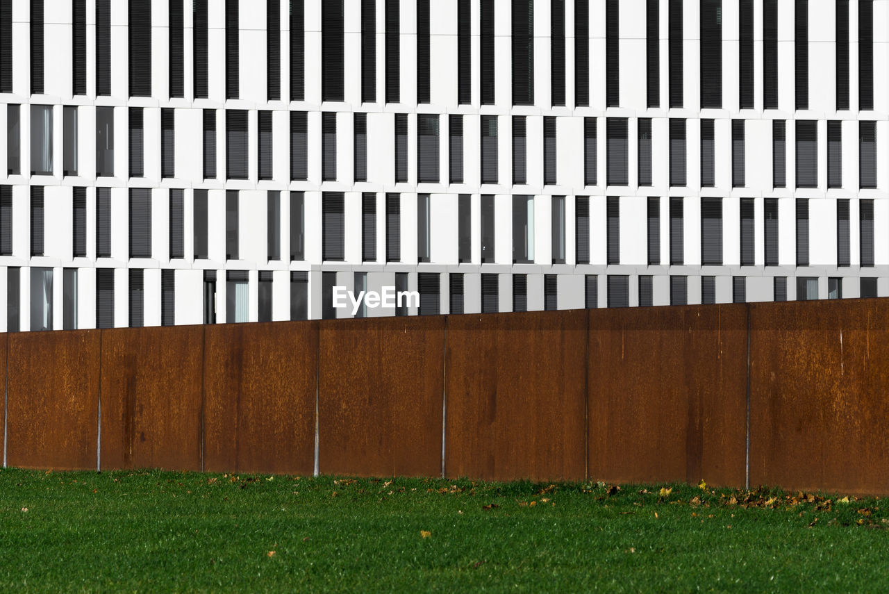 grass, barrier, wood - material, boundary, no people, fence, pattern, day, architecture, plant, nature, built structure, outdoors, field, protection, land, green color, side by side, building exterior, security