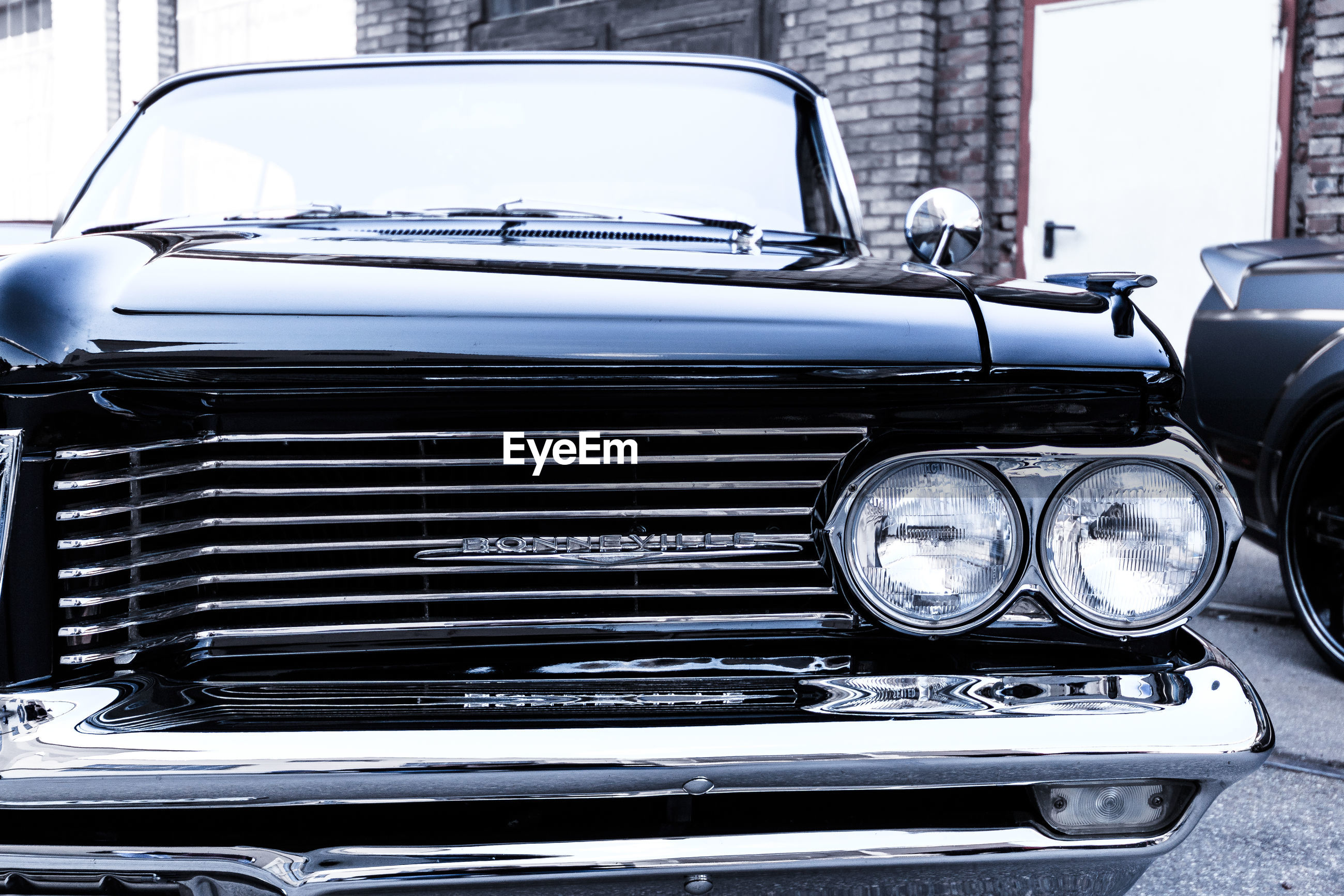 car, mode of transportation, land vehicle, motor vehicle, transportation, headlight, retro styled, vintage car, day, no people, stationary, close-up, metal, outdoors, luxury, vehicle hood, city, wealth, windshield, chrome, garage