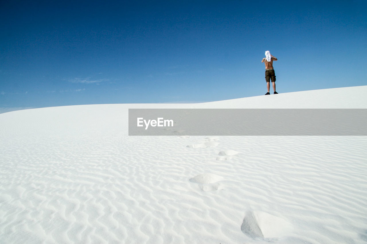 Man Standing On Sand Dune Against Clear Sky