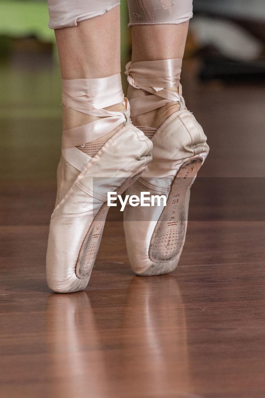 Low Section Of Ballerina Standing Tiptoe On Hardwood Floor