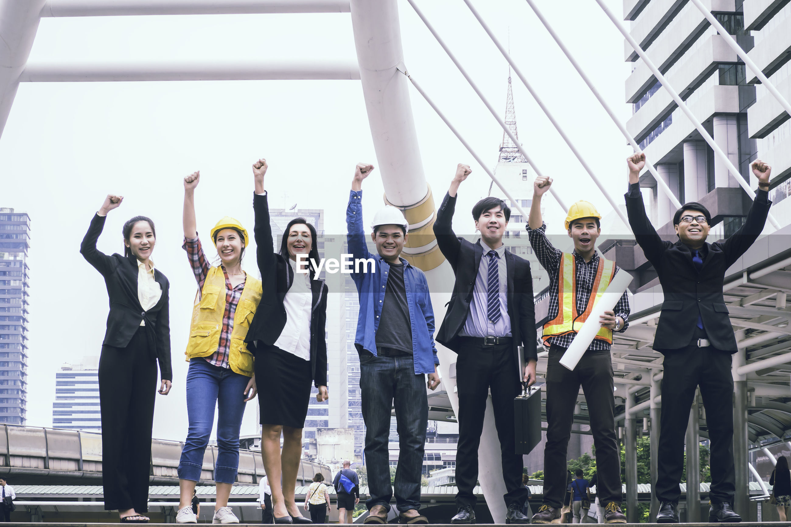 Portrait of engineers and business people with arms raised standing outdoors