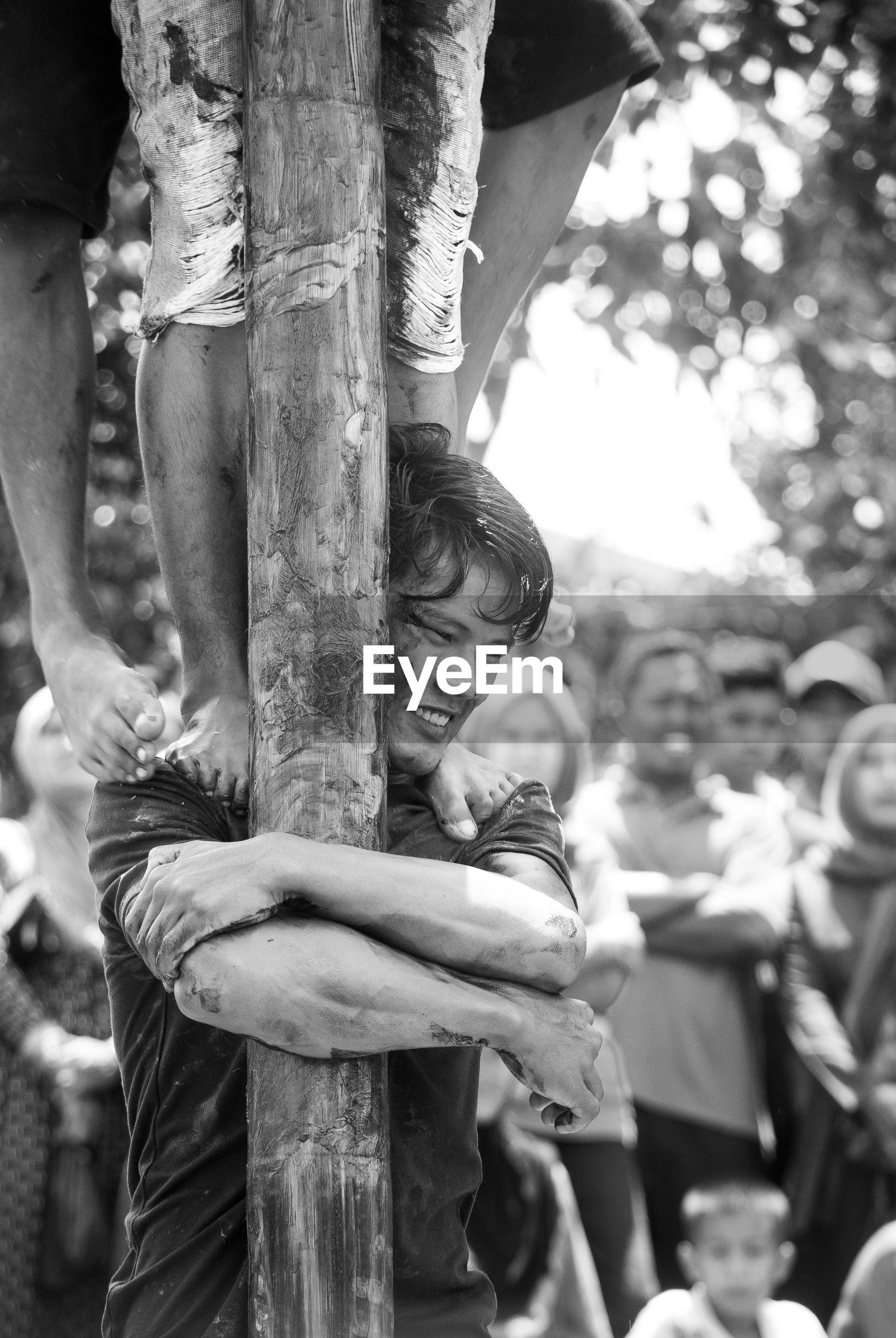 Close-up of man embracing pole while playing panjat pinang