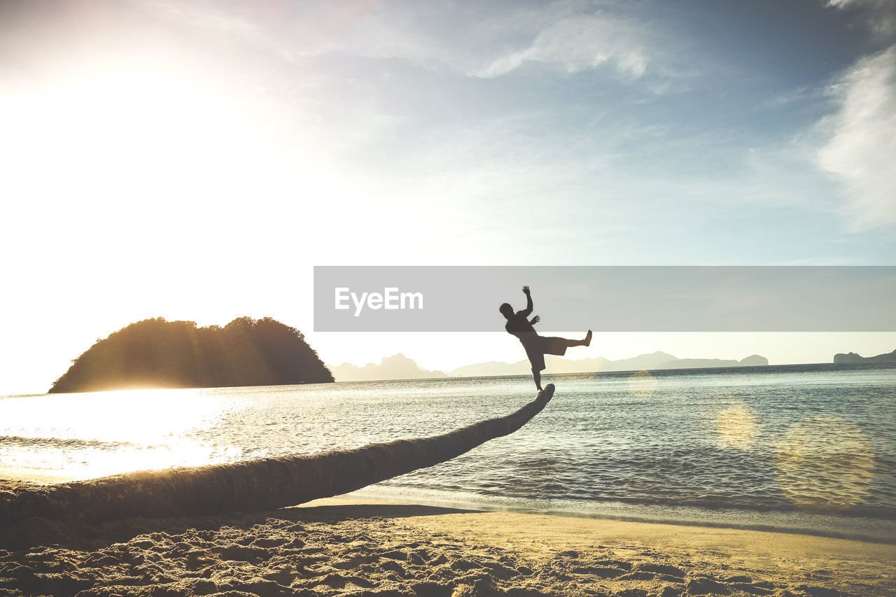 Silhouette Man Balancing On Log At Sea Shore Against Sky
