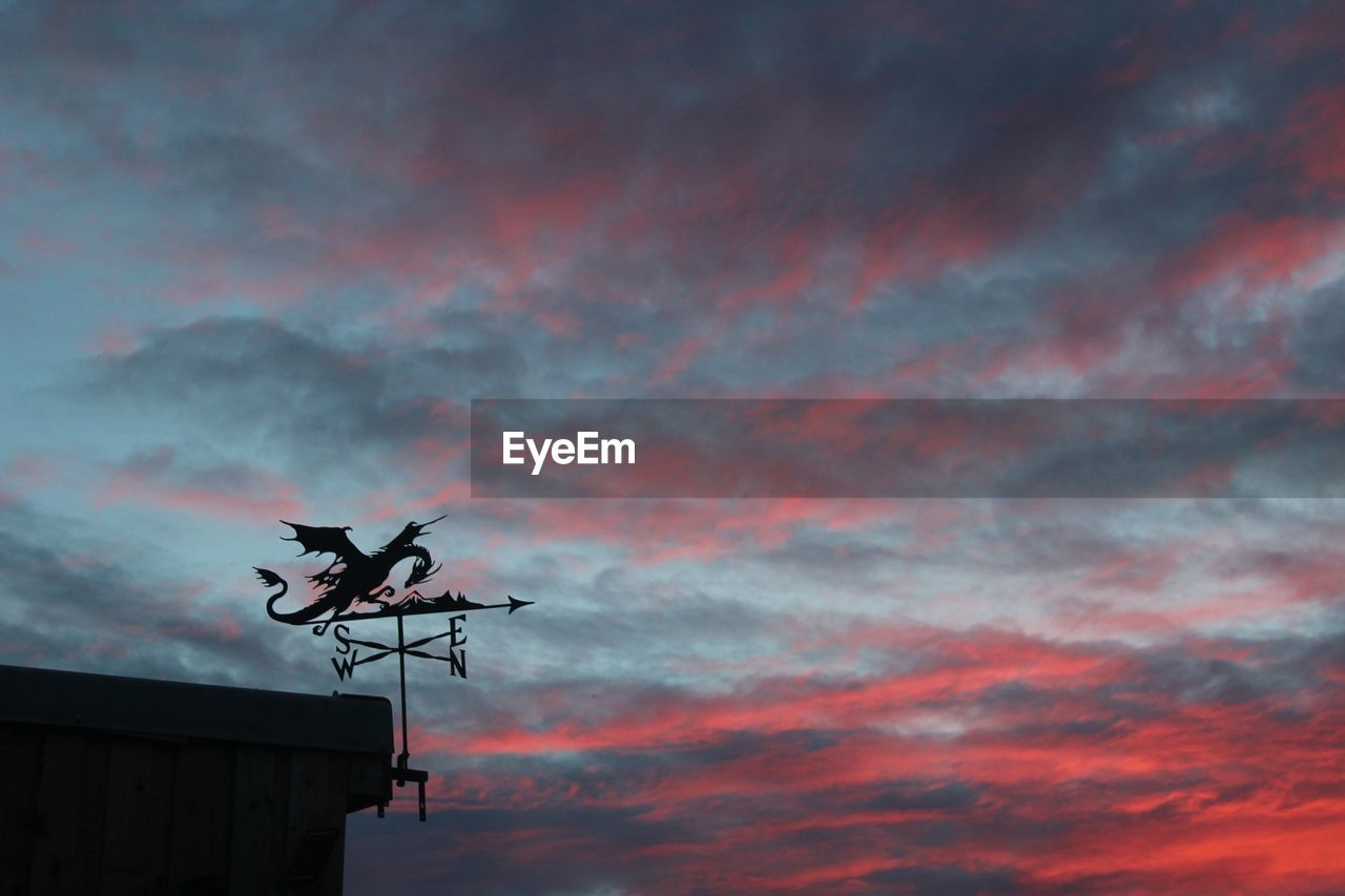 Silhouette Of Weather Vane Against Cloudy Sky