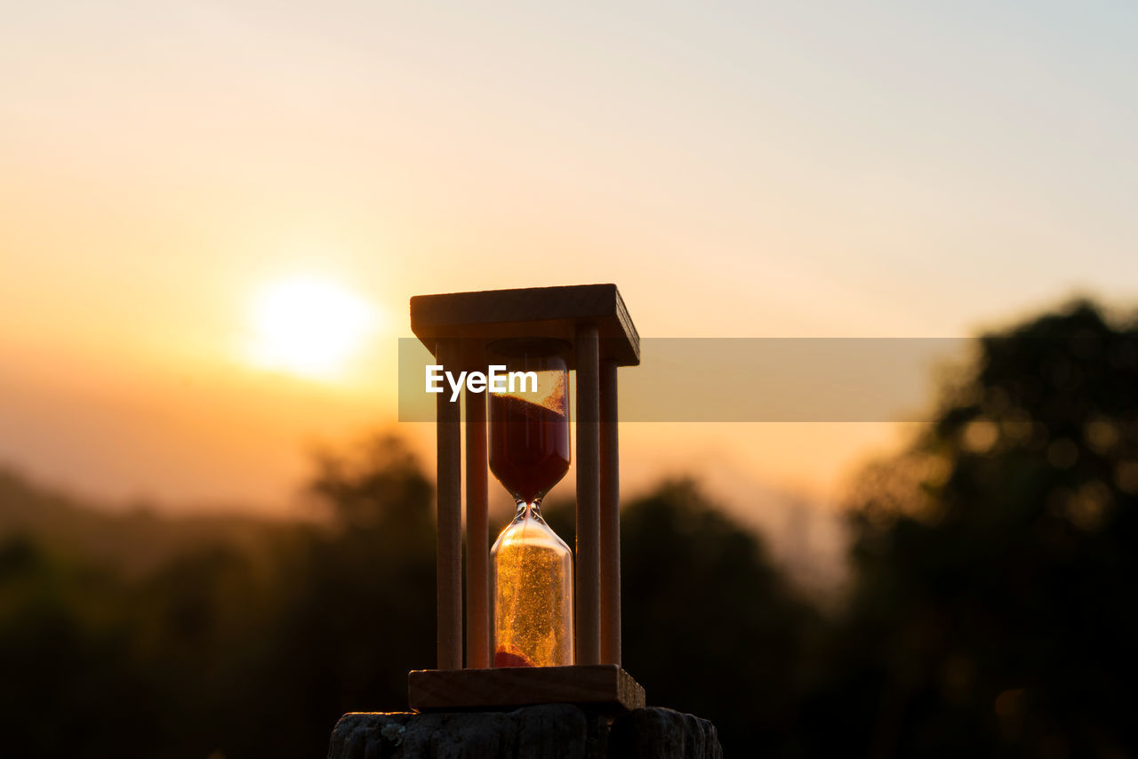 sunset, sky, orange color, sun, nature, focus on foreground, no people, sunlight, silhouette, beauty in nature, scenics - nature, outdoors, close-up, copy space, plant, non-urban scene, tranquility, selective focus, tranquil scene, tree