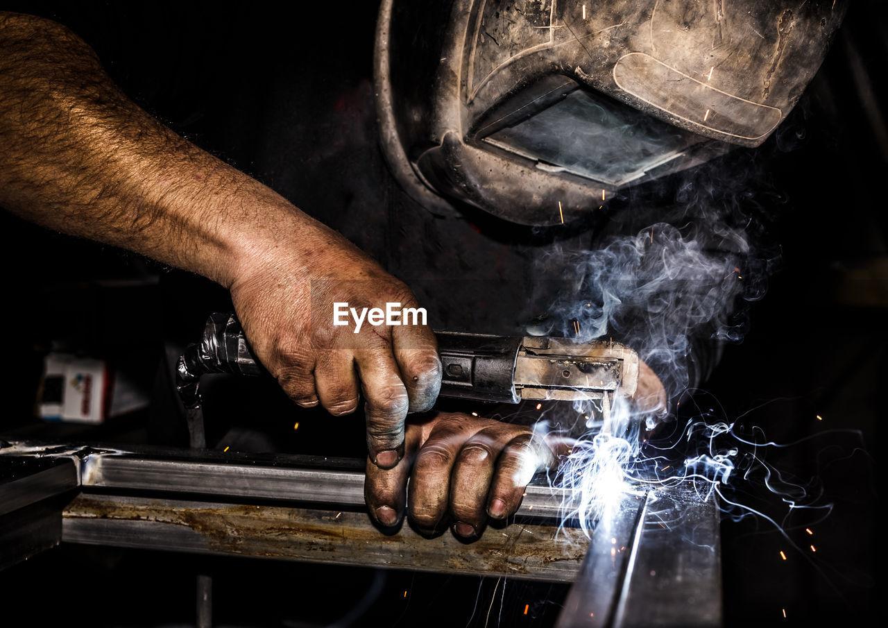 Close-Up Of Male Welder Welding Metal In Factory