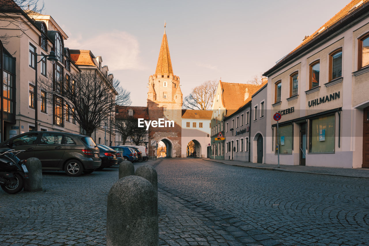 architecture, built structure, building exterior, city, building, street, religion, transportation, mode of transportation, motor vehicle, place of worship, sky, car, spirituality, belief, land vehicle, cobblestone, residential district, outdoors, spire