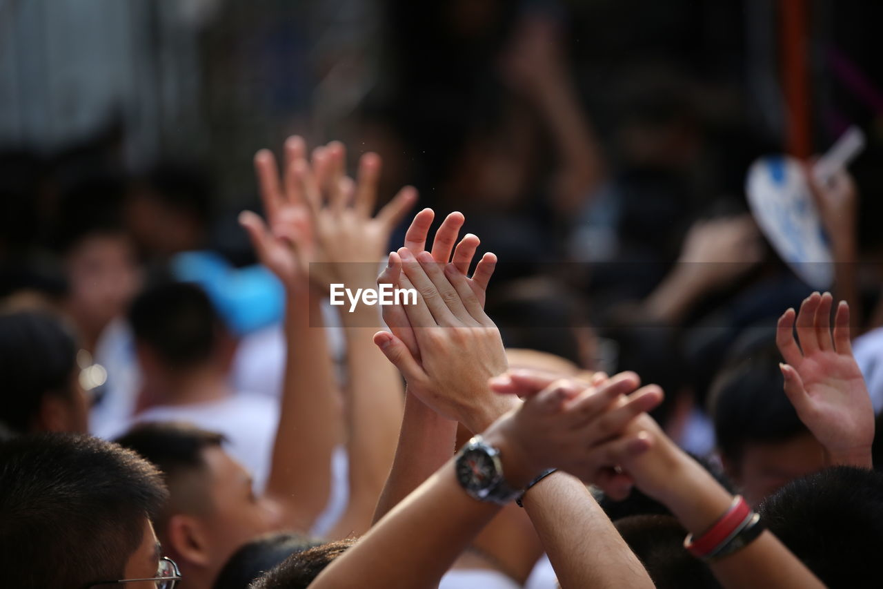 Crowd clapping hands during event