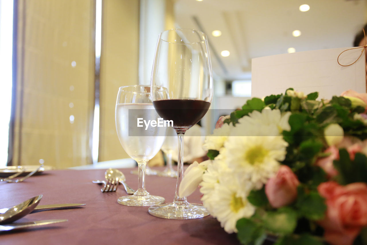 glass, wineglass, wine, refreshment, table, drink, alcohol, freshness, food and drink, flower, indoors, flowering plant, business, no people, still life, restaurant, glass - material, plant, drinking glass, red wine, setting, flower arrangement, luxury, flower head, bouquet, dining