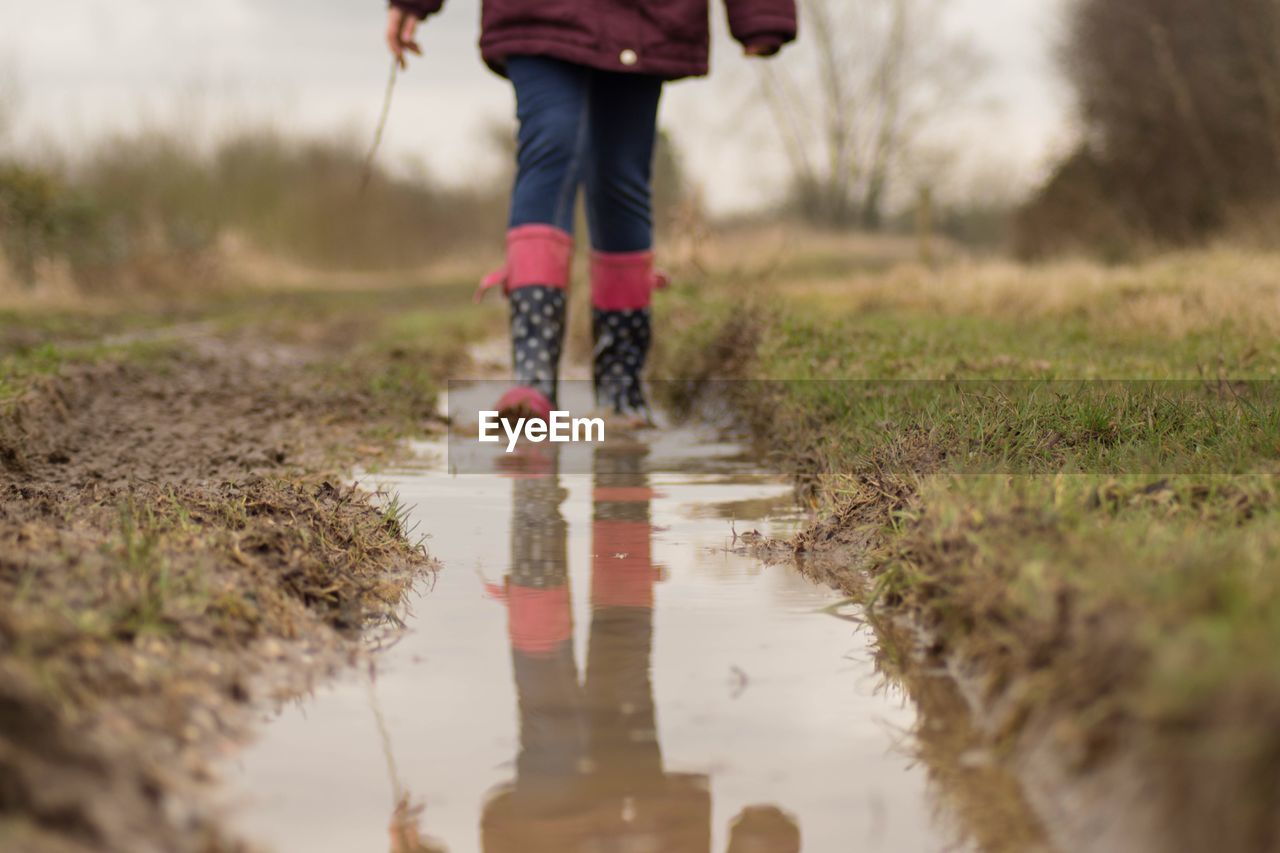 Low Section Of Girl Walking In Puddle