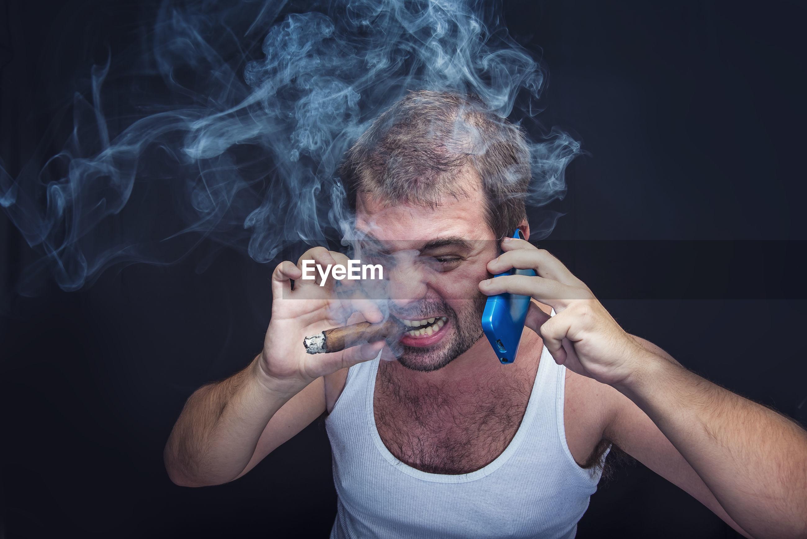 Close-up portrait of man smoking over black background