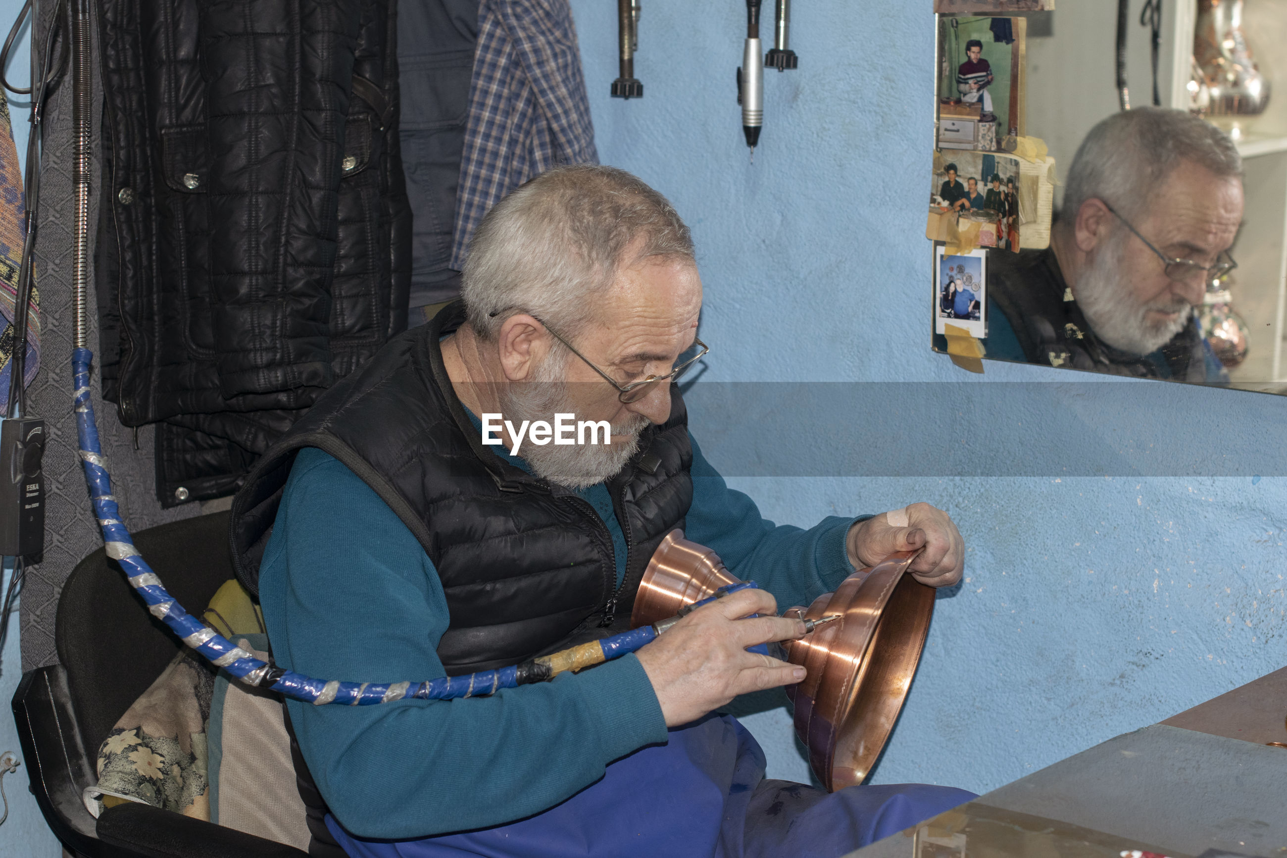 Senior man carving on brass container while sitting in workshop
