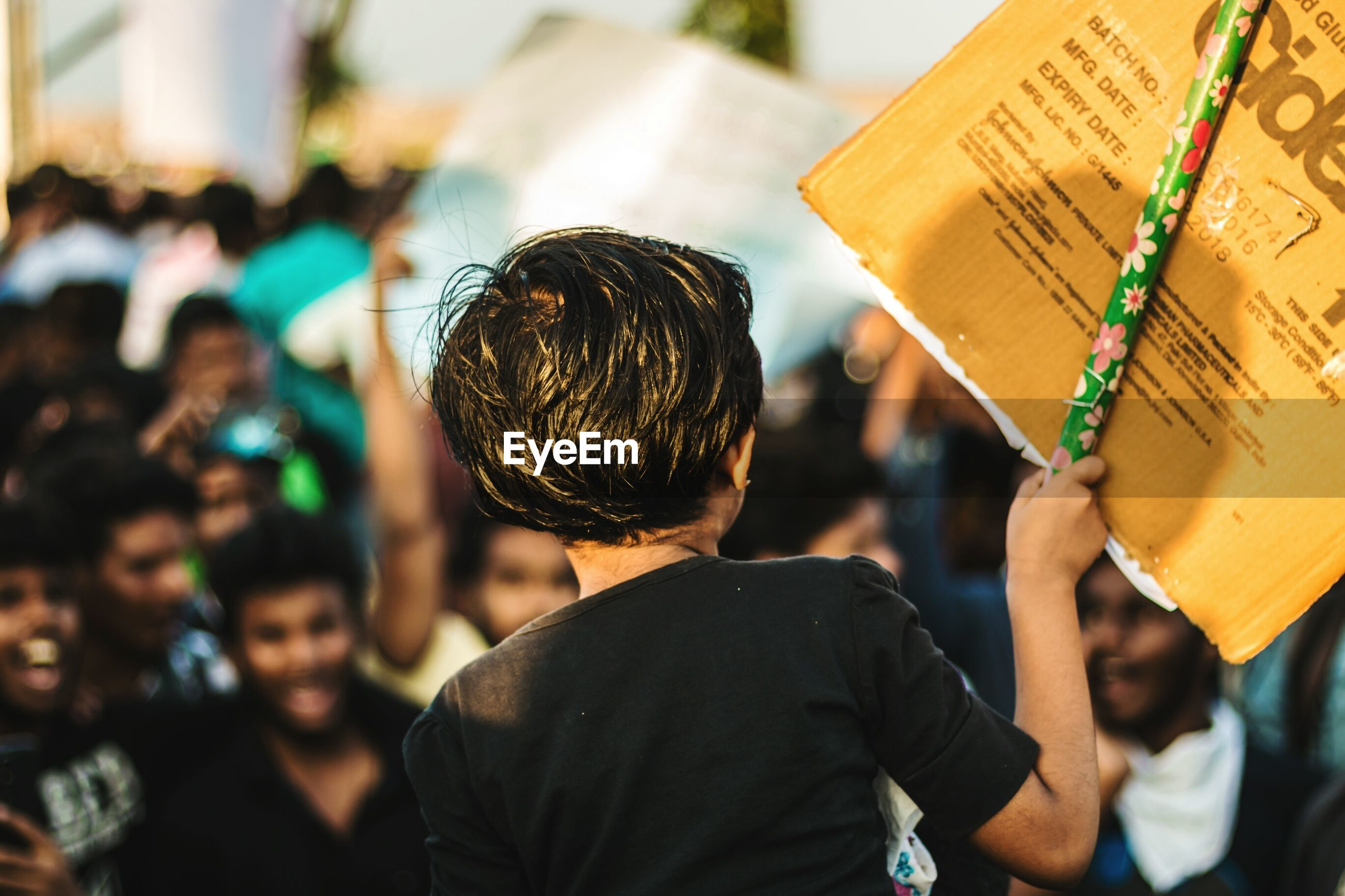 Rear view of girl holding banner during protest