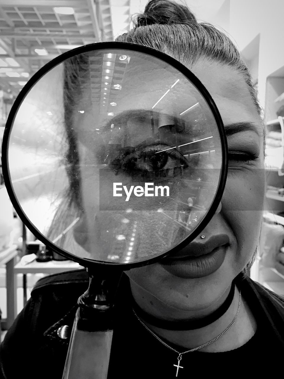 Portrait of woman looking through magnifying glass