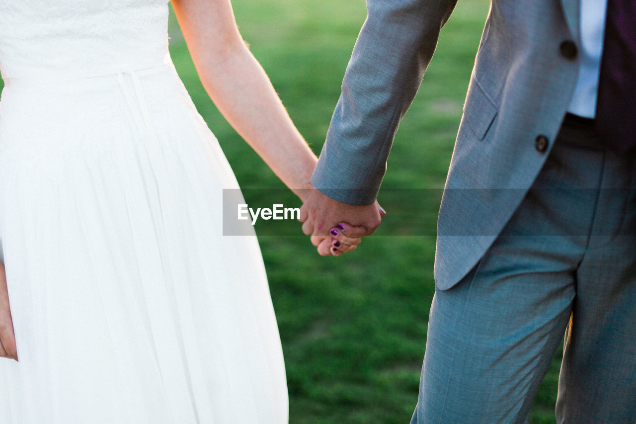 Midsection of wedding couple holding hands while standing on field