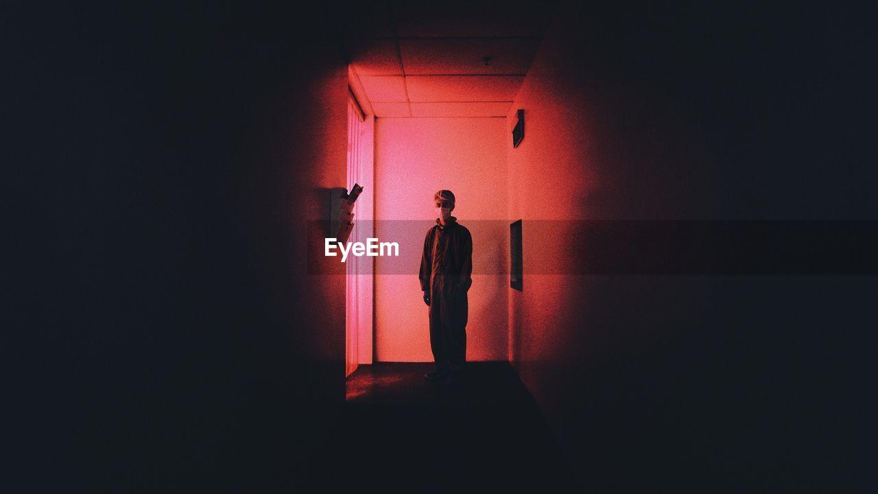 Young Man Standing In Darkroom