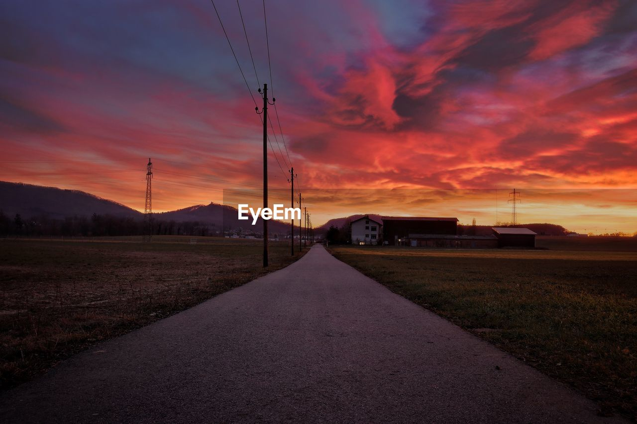 sky, cloud - sky, sunset, road, transportation, the way forward, no people, direction, nature, scenics - nature, land, cable, electricity, field, landscape, orange color, technology, beauty in nature, diminishing perspective, environment, outdoors, power supply, telephone line