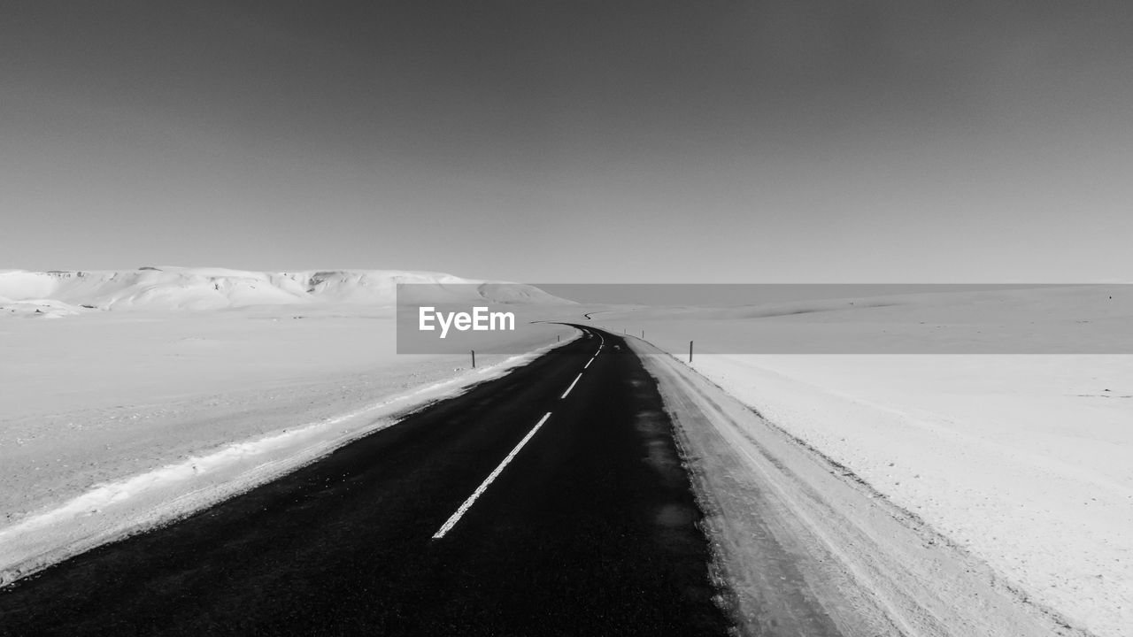 road, transportation, the way forward, direction, snow, sky, cold temperature, winter, landscape, nature, environment, sign, scenics - nature, beauty in nature, non-urban scene, no people, copy space, diminishing perspective, tranquil scene, outdoors, snowcapped mountain