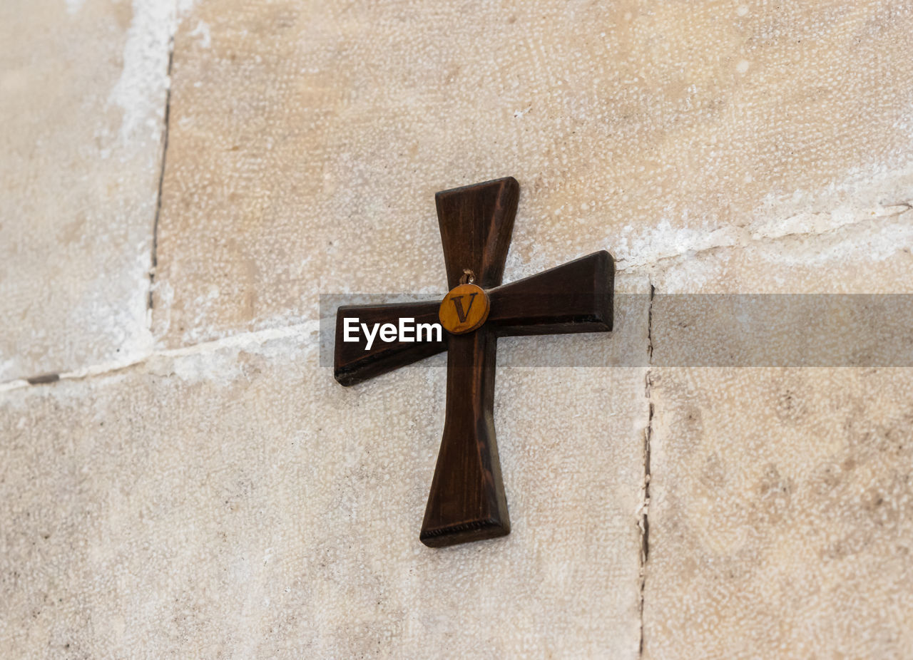cross, wall - building feature, no people, religion, day, close-up, spirituality, belief, architecture, outdoors, built structure, crucifix, wall, wood - material, solid, hanging, cross shape, building exterior, concrete, stone wall, religious equipment