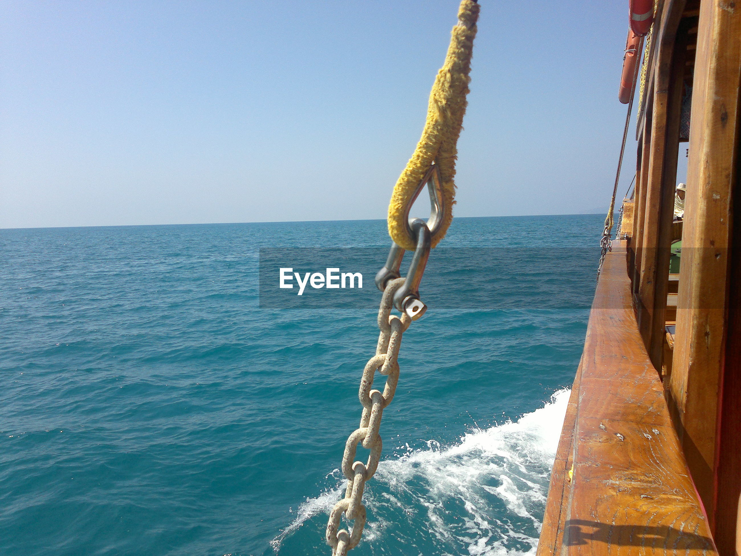 Chain hanging on boat over sea against clear sky