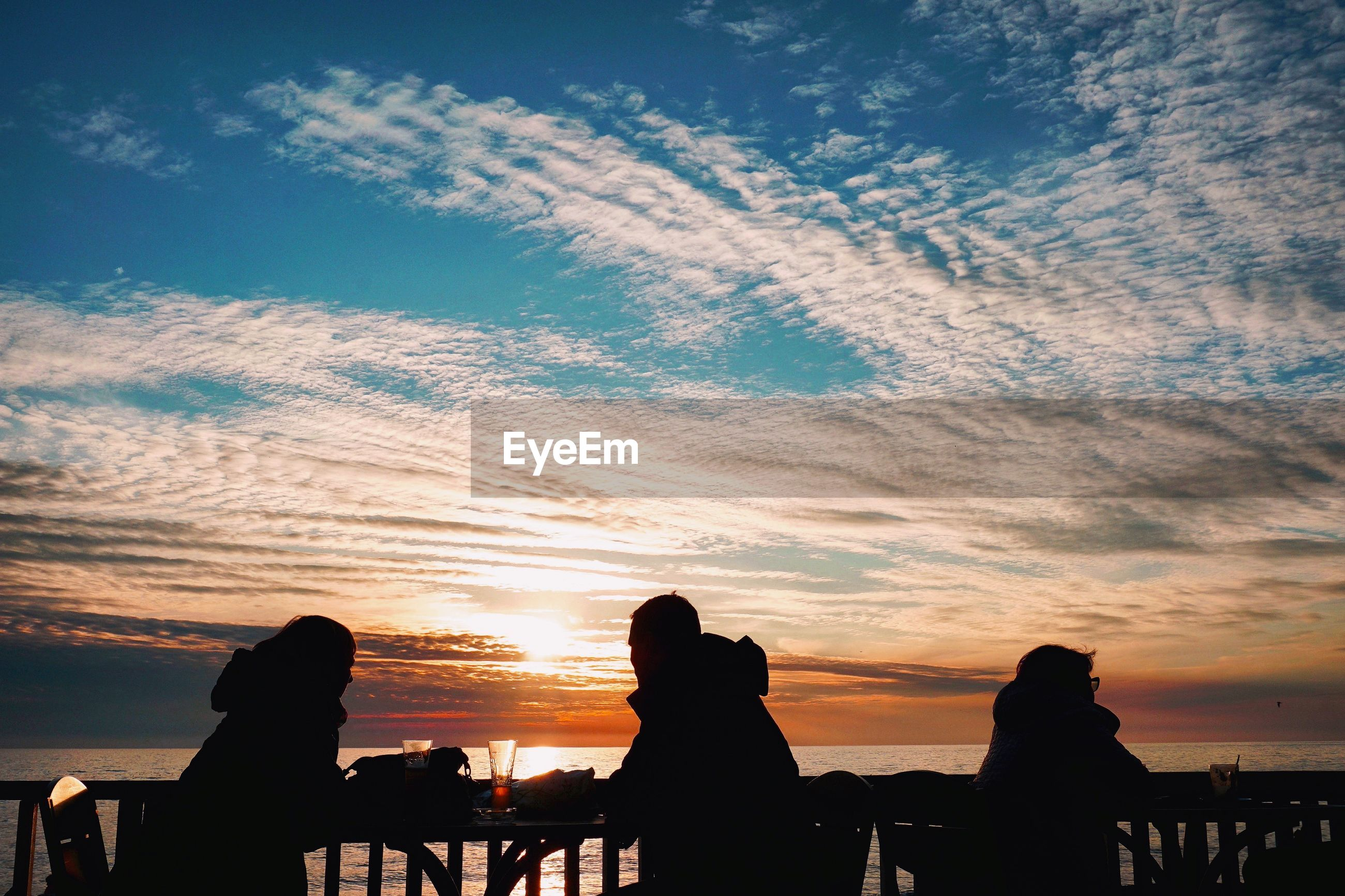 Silhouette people sitting at table by sea against cloudy sky during sunset