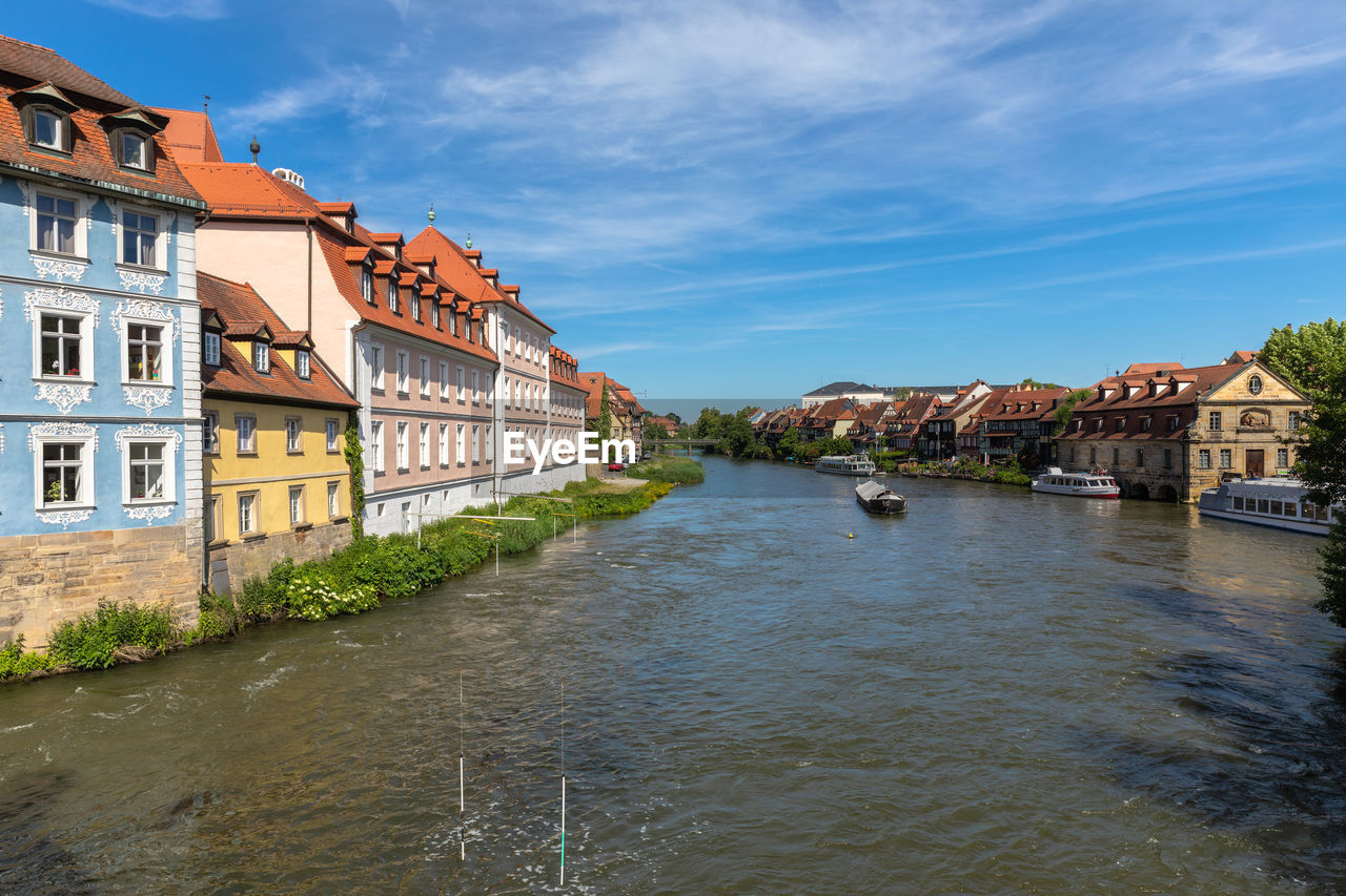 RIVER AMIDST BUILDINGS IN CITY