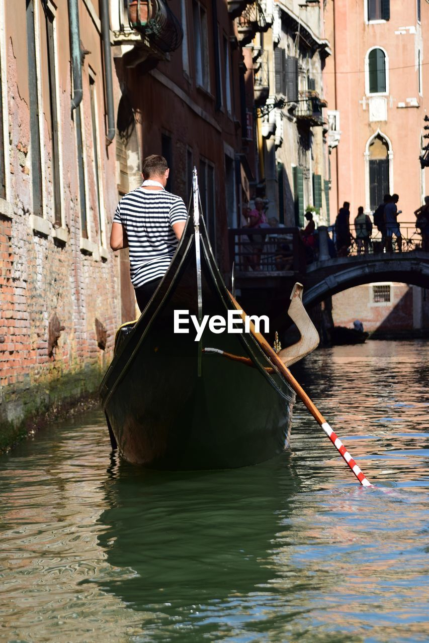 Rear View Of Man On Gondola Sailing In Canal