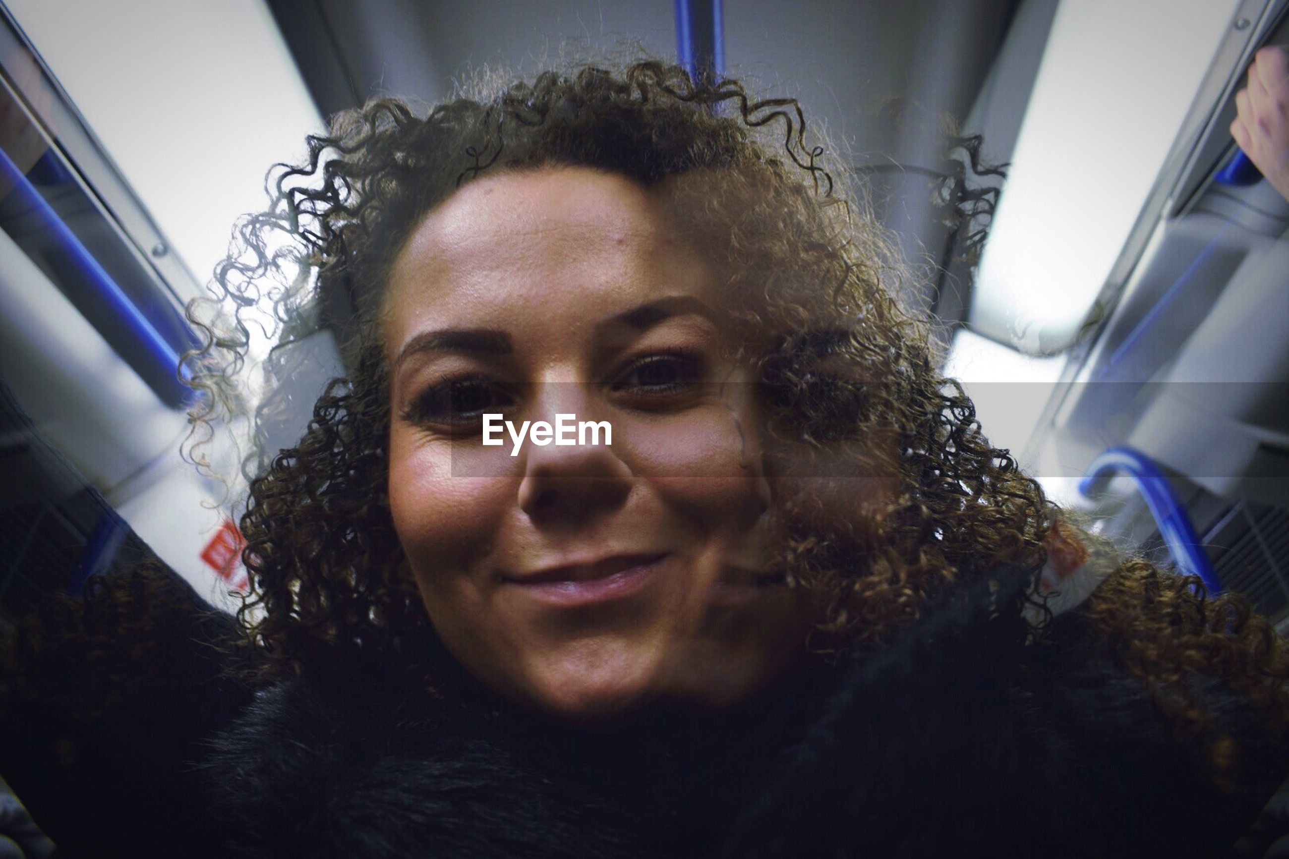 Low angle portrait of woman with curly hair in train